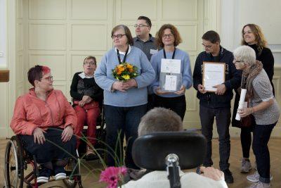 Mehrere Menschen stehen aufgereiht mit einem Blumenstrauß und einem gerahmten Bild auf der Bühne.