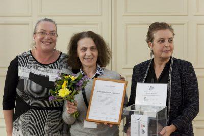 Drei Frauen stehen aufgereiht mit einem transparenten Einwurfkasten, Blumenstrauß und einem gerahmten Bild.